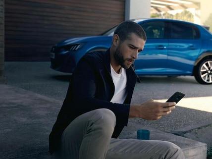 NEUER PEUGEOTe-208 – Mann mit Smartphone, App MyPeugeot